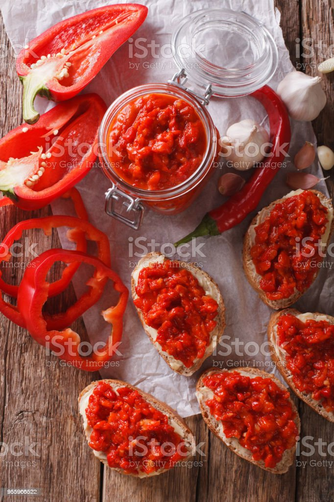 Ajvar in a glass jar and toast on a wooden background. Vertical top view stock photo
