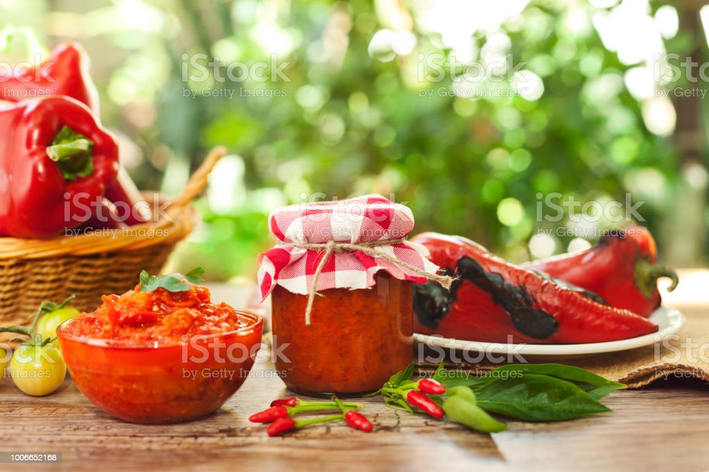 Ajvar in a jar and glass bowl stock photo