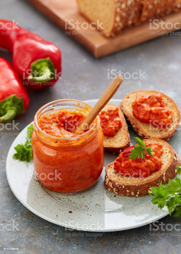 Ajvar (pepper mousse) in a jar and on a slices of bread stock photo