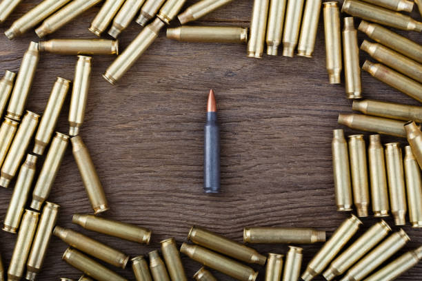 Ak-47 cartridges on wooden table close-up stock photo