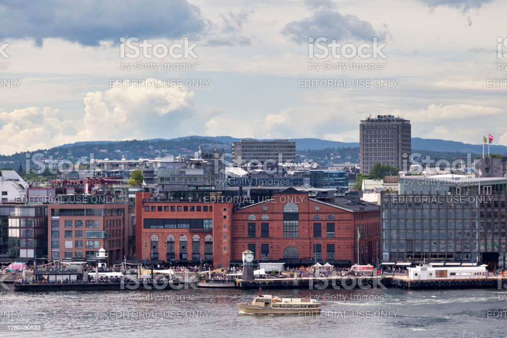 Aker Bruges in Oslo Oslo, Norway - June 26 2019: View of the neighbourhood of Aker Brygge on the westside of Pipervika (an arm of the Oslo Fjord), with the buildings of the former workshop hall and machine hall as well as the clock tower. Aerial View Stock Photo