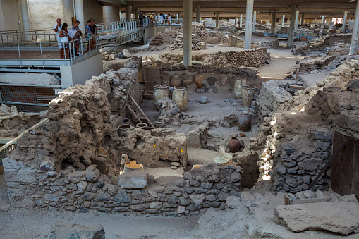 Akrotiri, Santorini Island, Greece - July 04, 2018: Akrotiri is an archaeological site from the  Cycladic Bronze Age on the Santorini Island. You can see ancient buildings, decorated pottery and people on the site.