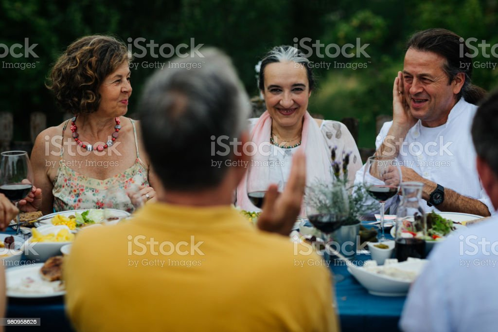 Group of friends sitting, talking and enjoying al fresco dining.