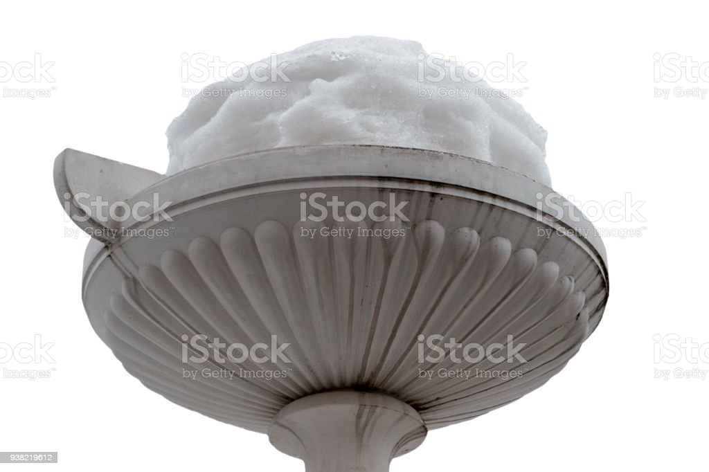 Alabaster garden urn or vase with a large cap of snow stock photo