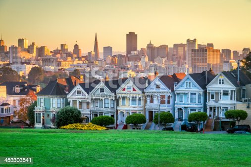 Classic shot of Victorian houses across the street from Alamo Square in San Francisco. Skyline of San Francisco is seen in background.