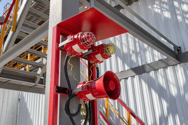 Alarm and emergency warning system installed on the territory of the petrochemical complex Alarm system consisting of a megaphone and two warning lights at the factory military attack stock pictures, royalty-free photos & images