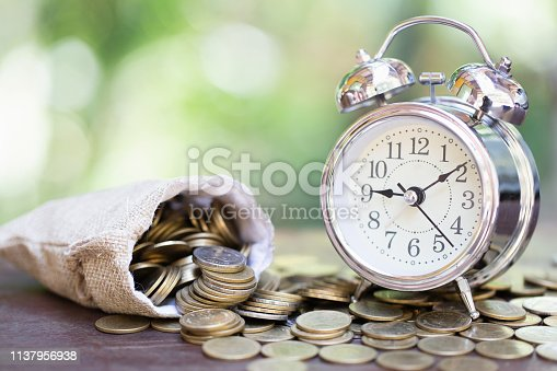 istock Alarm clock and a pile of golden coins on the table, Concept of opportunity cost time and Money saving. Investment risk 1137956938