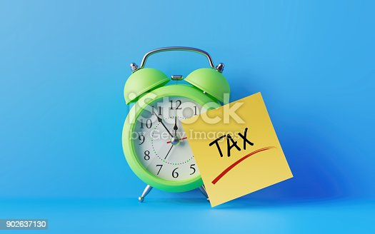 istock Alarm Clock And A yellow Post It Not Over Blue Background 902637130