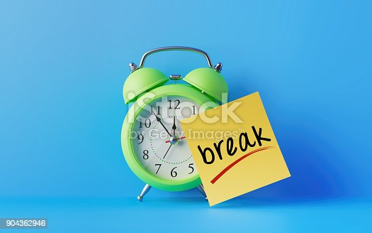 Green alarm clock with a yellow post it note attached over bright blue background. Break writes on post it note. Reminder concept. Horizontal composition with copy space.