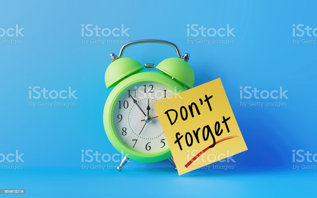 Alarm Clock And A Yellow Post It Note Over Blue Background stock photo