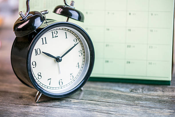 alarm clock and calendar on wooden table stock photo