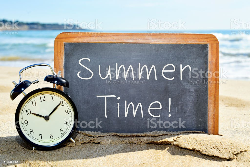 alarm clock and chalkboard with the text summer time stock photo