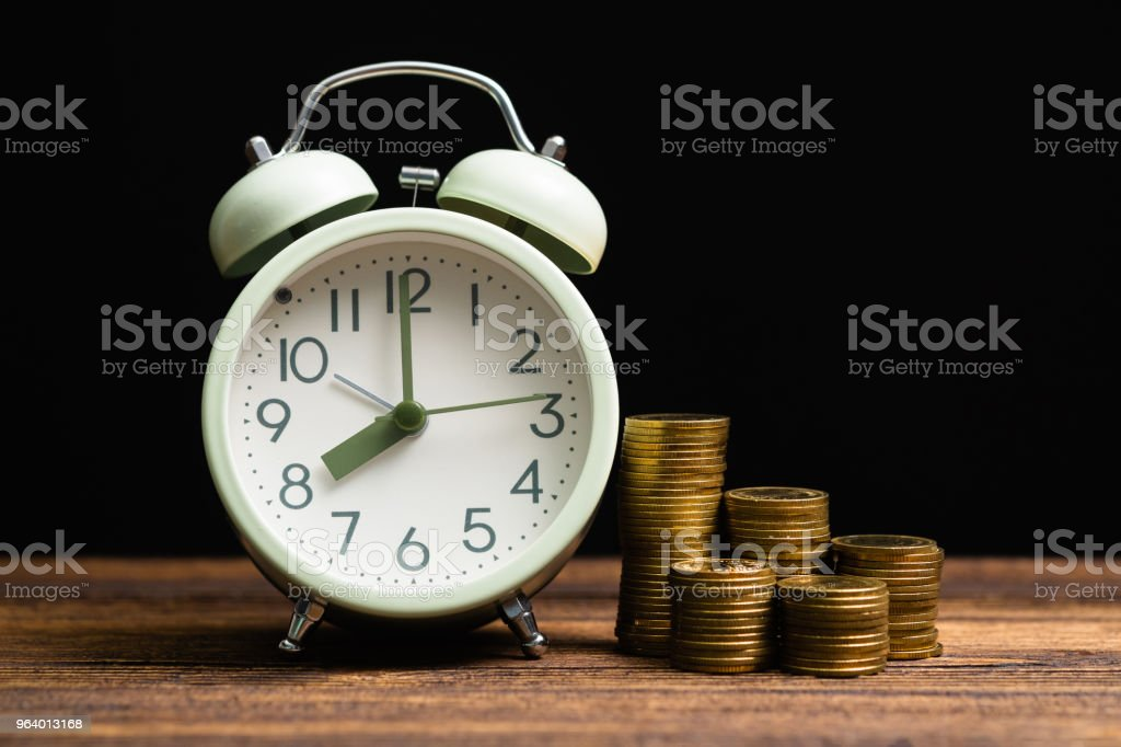 Alarm clock and coins stacks on working table in dark room, time for savings money concept, banking and business concept. - Royalty-free Accountancy Stock Photo