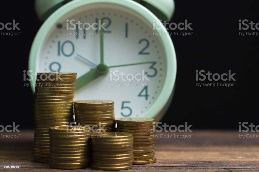 Alarm clock and coins stacks on working table in dark room, time for savings money concept, banking and business concept. zbiór zdjęć royalty-free