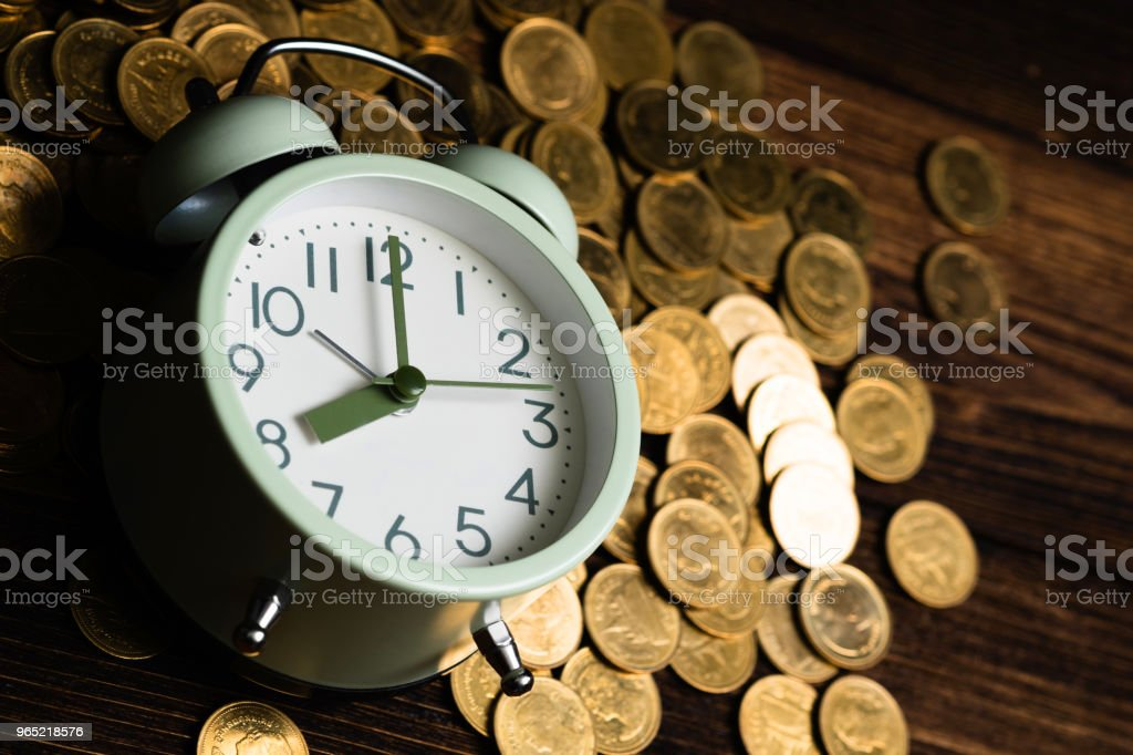 Alarm clock and coins stacks on working table in dark room, time for savings money concept, banking and business concept. royalty-free stock photo