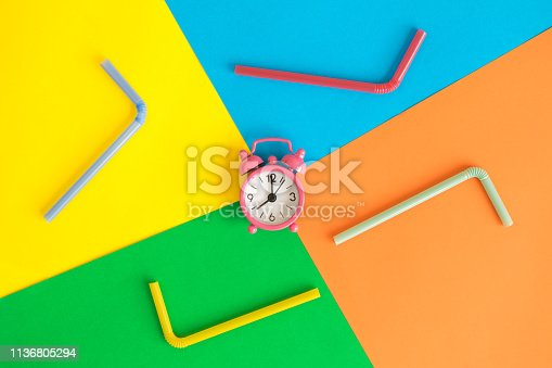 1139289535 istock photo Alarm clock and drinking straws on multicolored background summer abstract. 1136805294