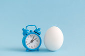 Alarm clock and egg isolated on blue. Space for copy. Easter minimalistic still life concept.