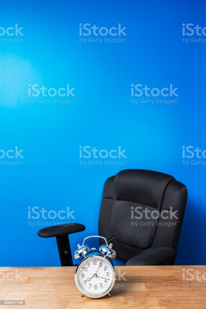 8:05AM Alarm Clock and Empty Office Chair stock photo