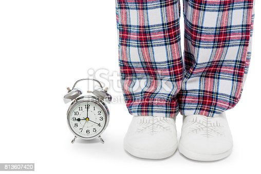 Alarm clock and female legs in pajamas and slippers on a white background closeup