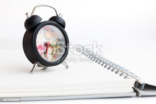 885959540 istock photo Alarm clock and notebook isolated on white 497099989