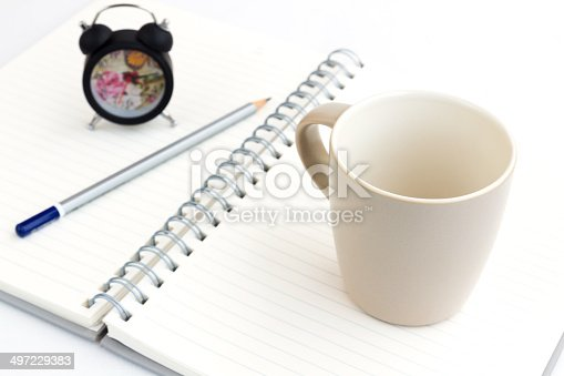 885959540istockphoto Alarm clock and notebook isolated on white 497229383