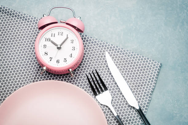 Alarm clock and plate with cutlery. Concept of intermittent fasting, lunchtime, diet and weight loss stock photo