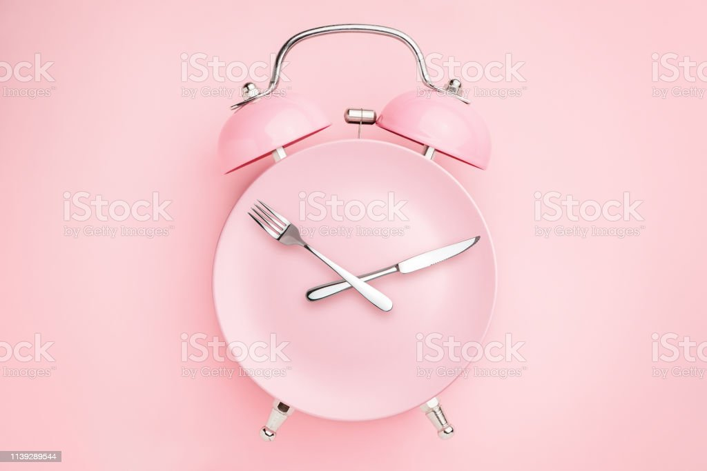 Alarm Clock And Plate With Cutlery Concept Of Intermittent Fasting  Lunchtime Diet And Weight Loss Stock Photo - Download Image Now