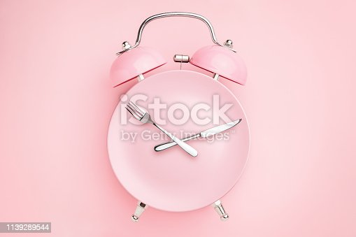 1139289535 istock photo Alarm clock and plate with cutlery . Concept of intermittent fasting, lunchtime, diet and weight loss 1139289544
