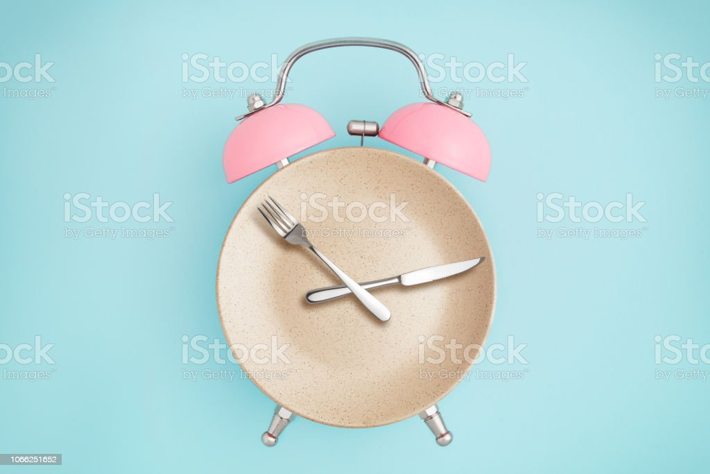 Alarm clock and plate with cutlery stock photo