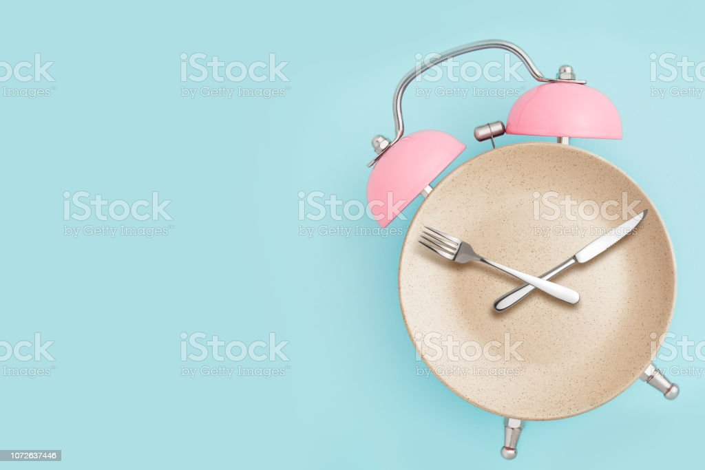 Alarm clock and plate with cutlery . stock photo