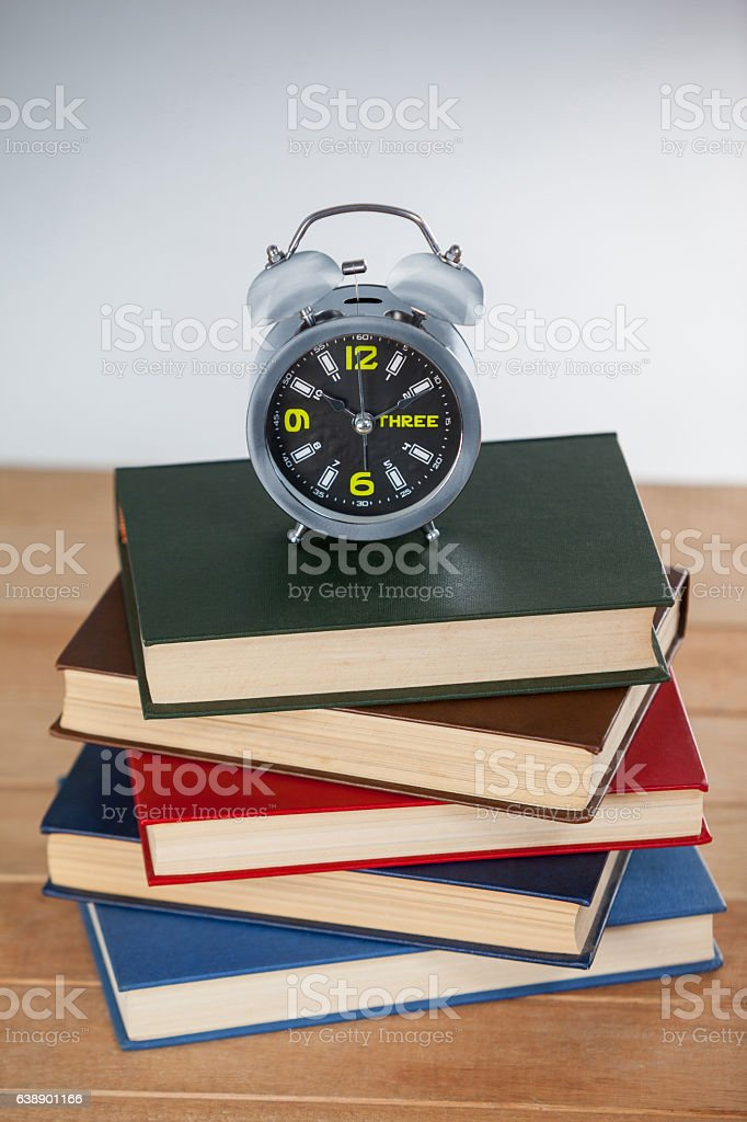Alarm clock and stack of books stock photo