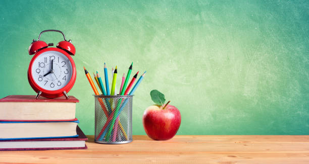 Alarm Clock And Stack Of Books With Pencils And Apple stock photo