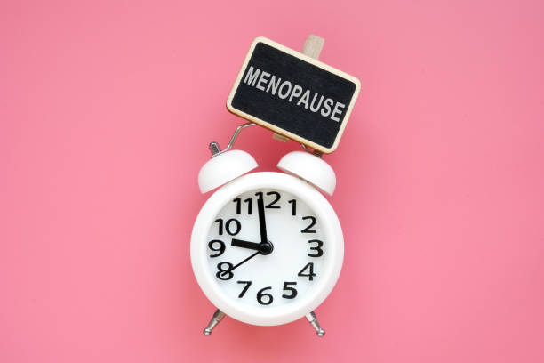 Wecker und Wortmenopause auf rosa Hintergrund. – Foto