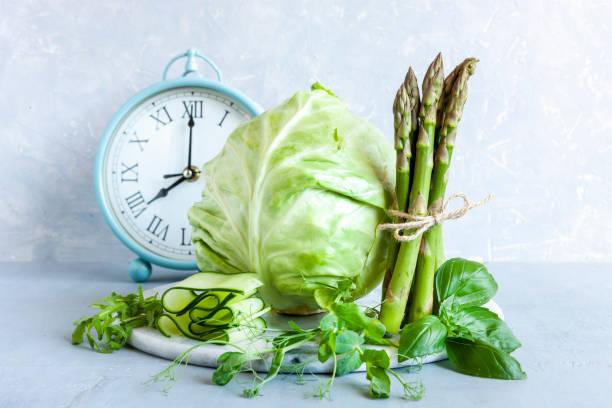 Despertador, Aspargos, microverdes, pepino e repolho - vegetais verdes frescos. Dieta cetogênica, jejum intermitente, perda de peso - foto de acervo