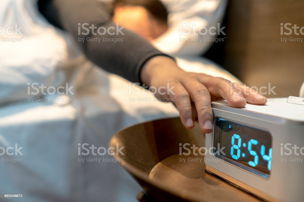 alarm clock at bedside stock photo