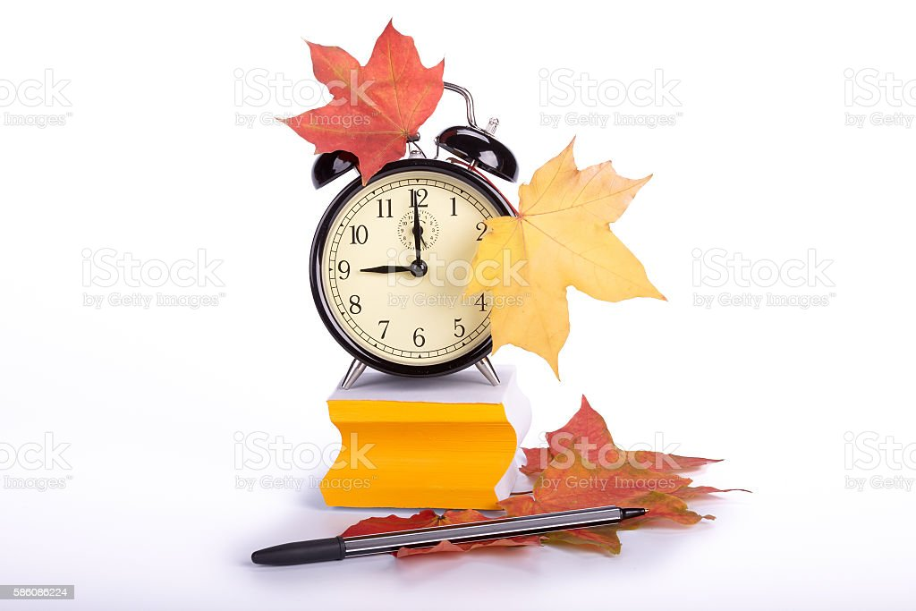 Alarm clock, autumn leaves, pen and stacked  blank papers stock photo