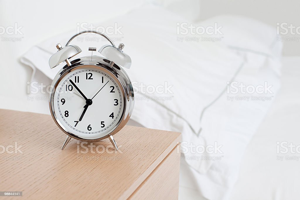 Alarm clock by bed royalty-free stock photo