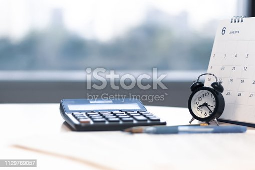 istock Alarm clock calculator and calendar on desk with city view background 1129769057