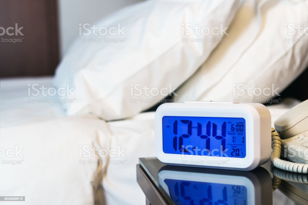 Alarm clock electronic stands on a bedside table near the bed stock photo