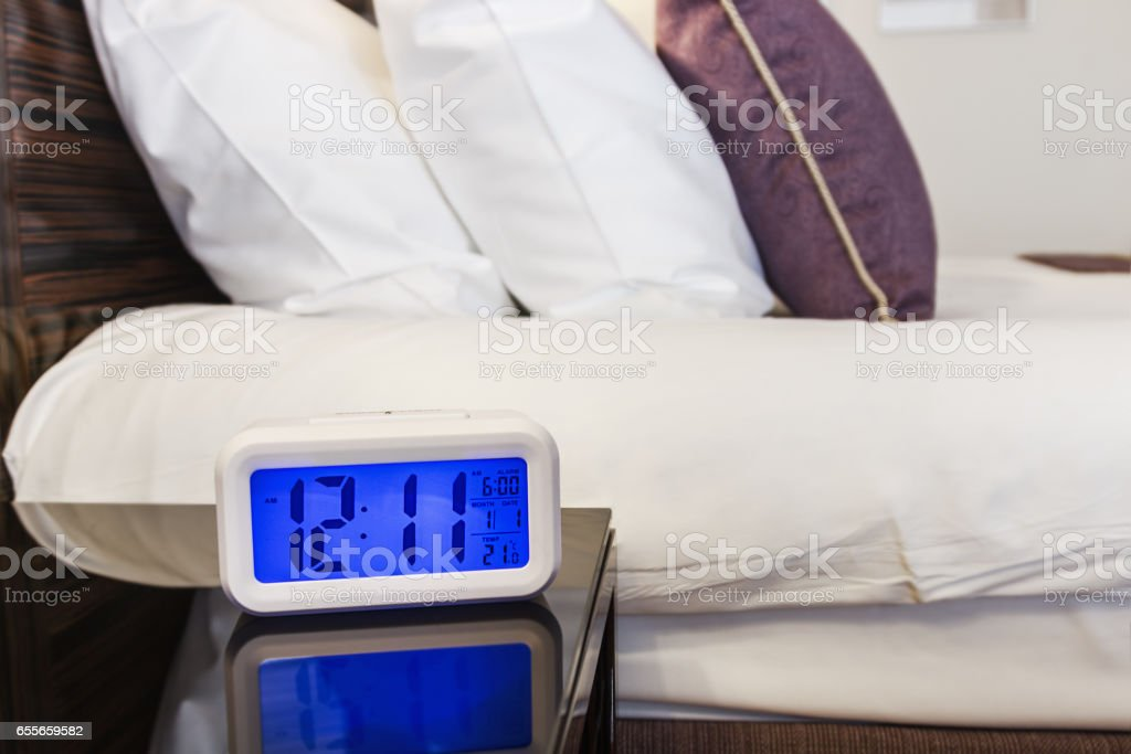 Alarm clock electronic stands on a bedside table stock photo