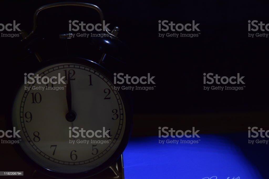 Alarm clock face on black background. education concept
