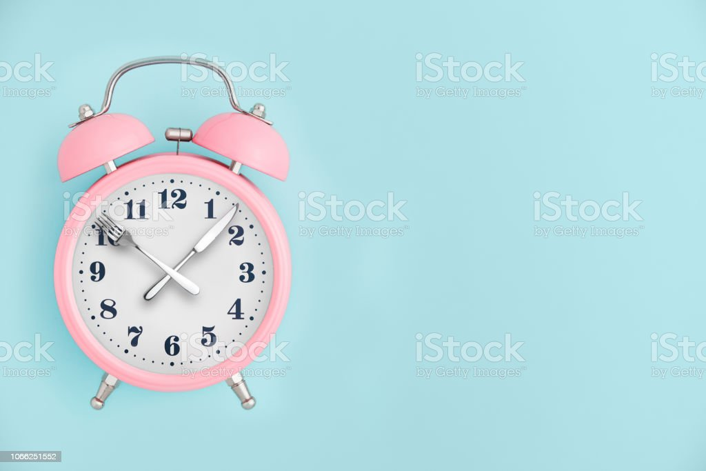 Alarm clock. Fork and knife instead of clock hands. Concept of...
