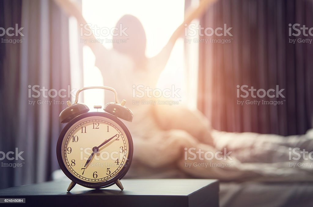 alarm clock having a good day in morning. Closeup alarm clock having a good day with background happy woman stretching in bed after waking up, sunlight in morning. 2016 Stock Photo