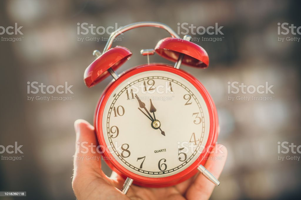 Red alarm clock in your hand. Midnight. New Year. Cracov in Poland.