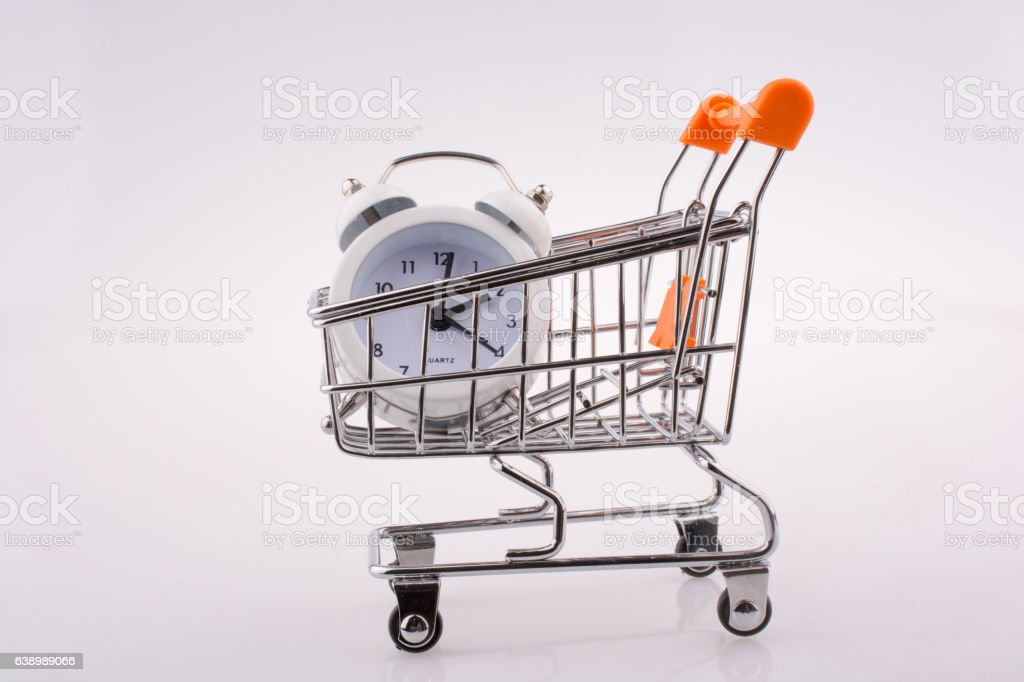 Alarm clock in shopping trolley on white background stock photo