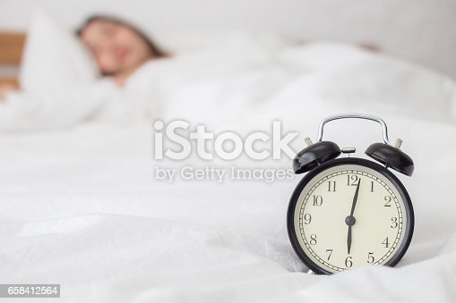 istock Alarm clock in the morning with woman sleep in background 658412564