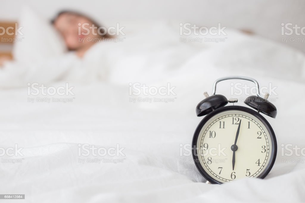 Relógio despertador de manhã com mulher dormir no fundo - foto de acervo