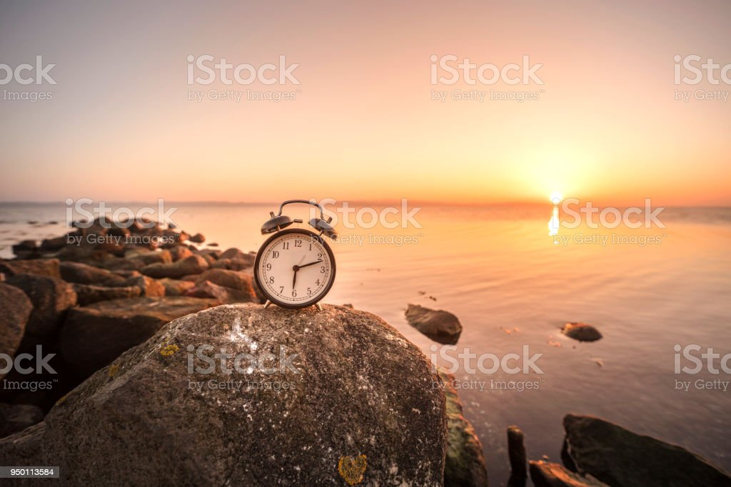Alarm clock in the sunrise by the sea stock photo