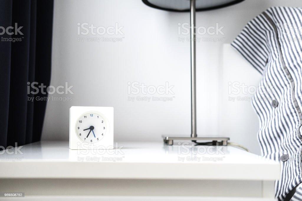 Alarm clock in white bedroom iterior