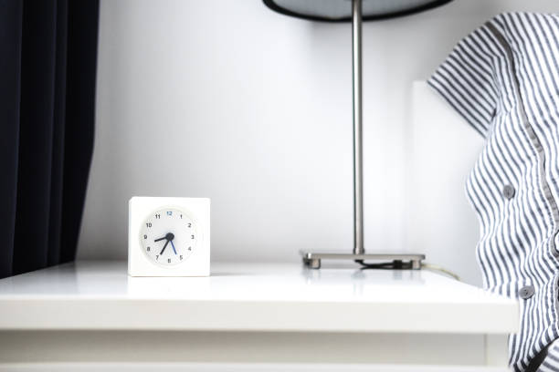 Alarm clock in white bedroom iterior stock photo
